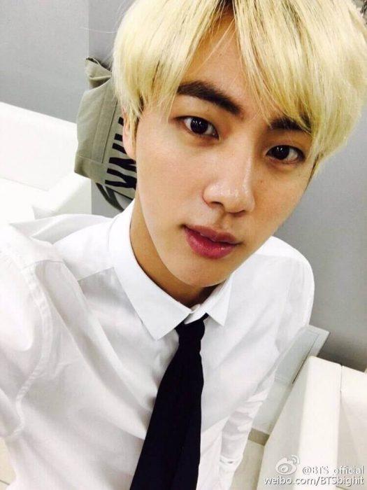 A blonde side part of Jin