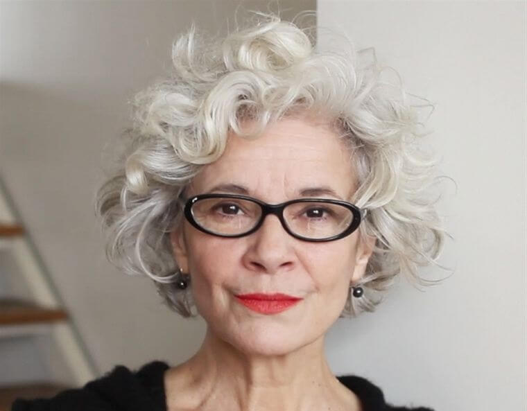 Hairstyle with curly hair for woman over 50 with glasses